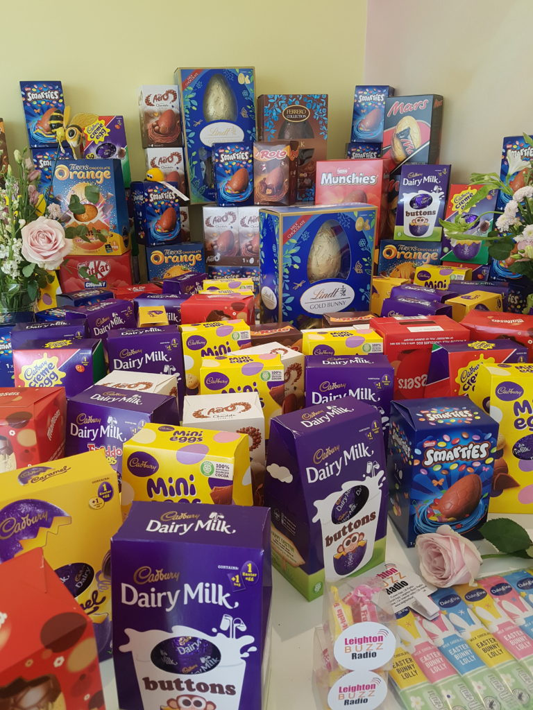 124 Easter eggs donated by Leighton Buzz Radio arranged on a table with spring flowers and yellow background